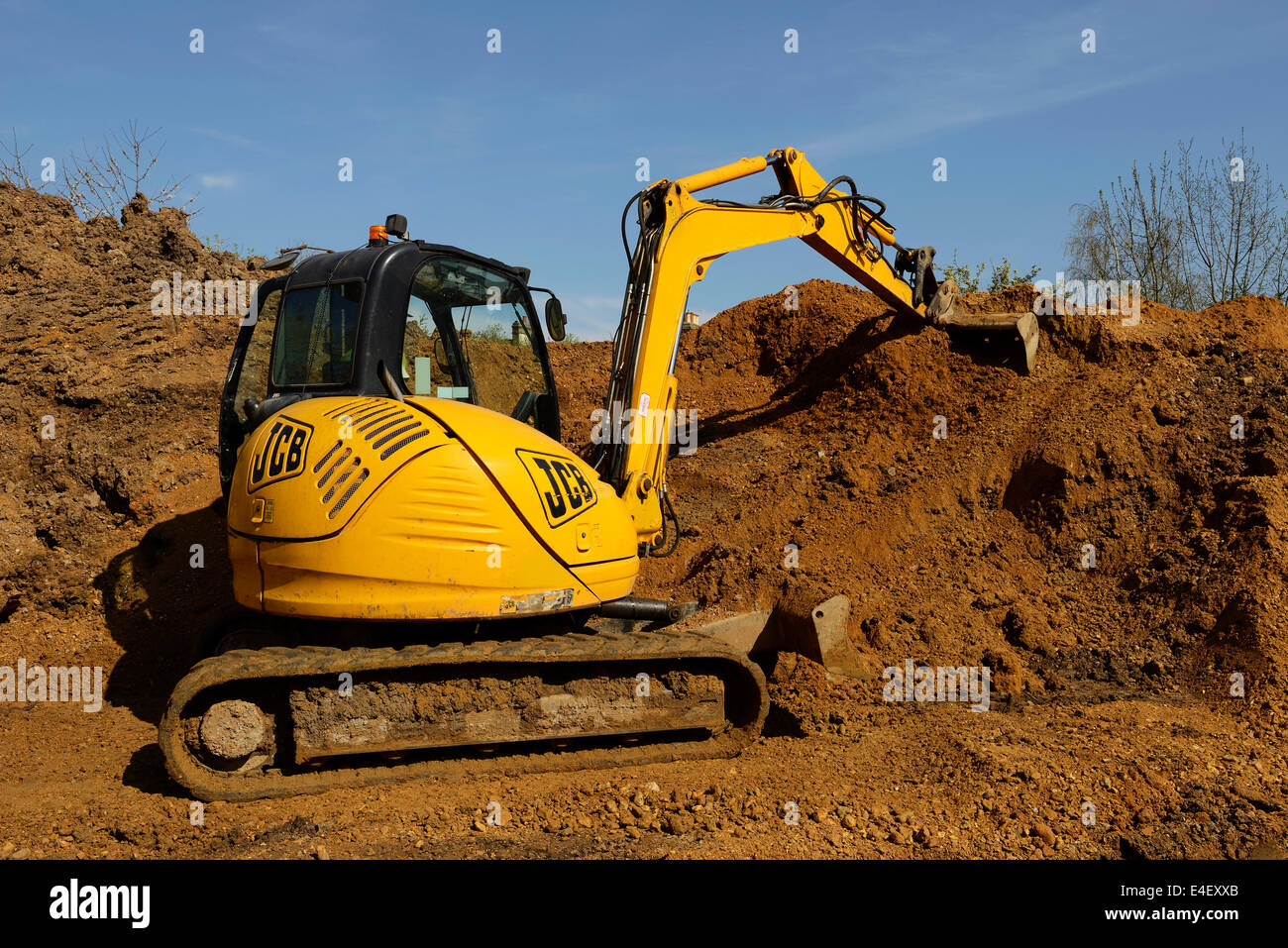 JCB digger moving earth on a construction site - Stock Image