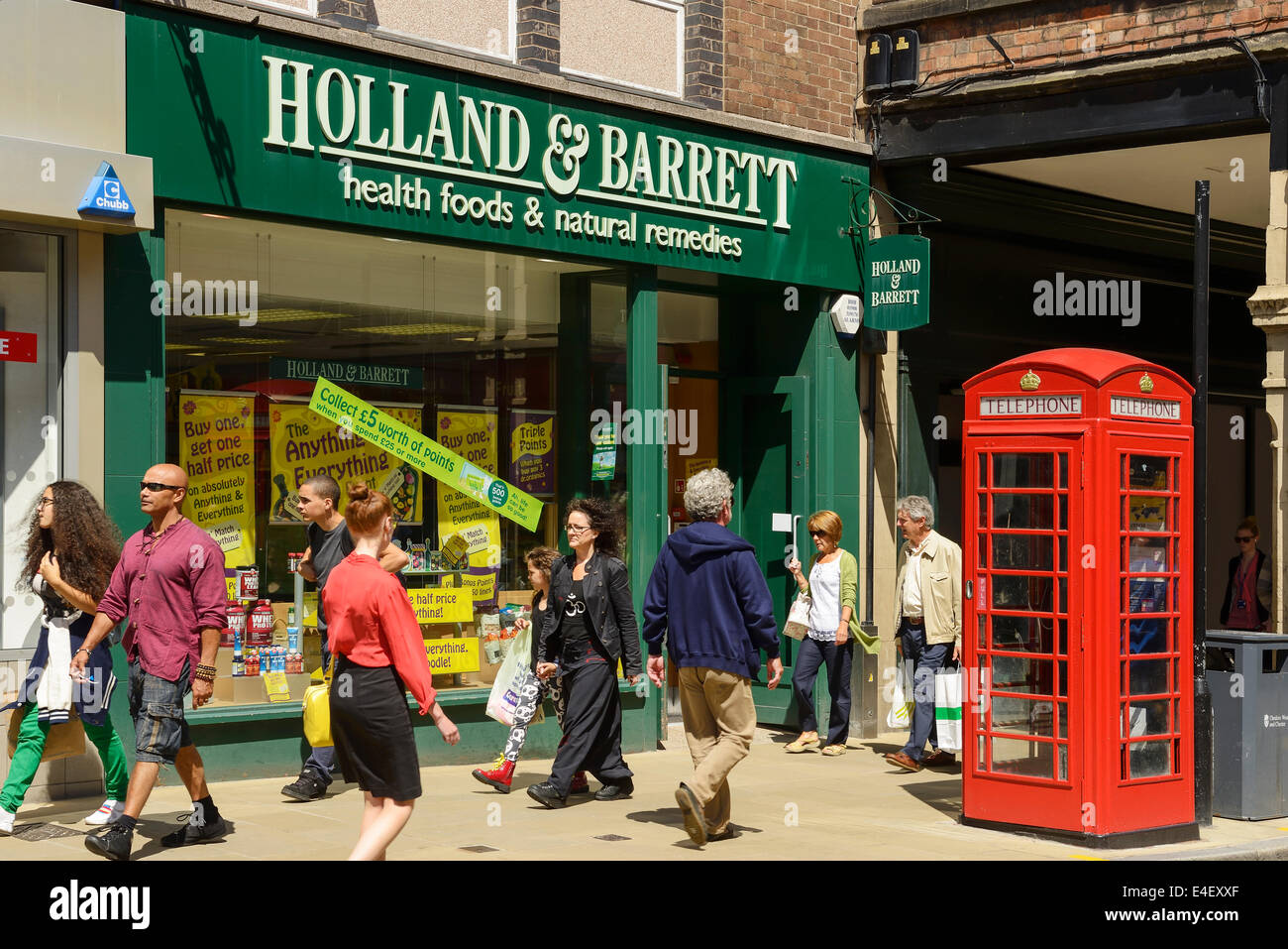 Shoppers in front of a Holland and Barrett store in Chester city centre UK - Stock Image