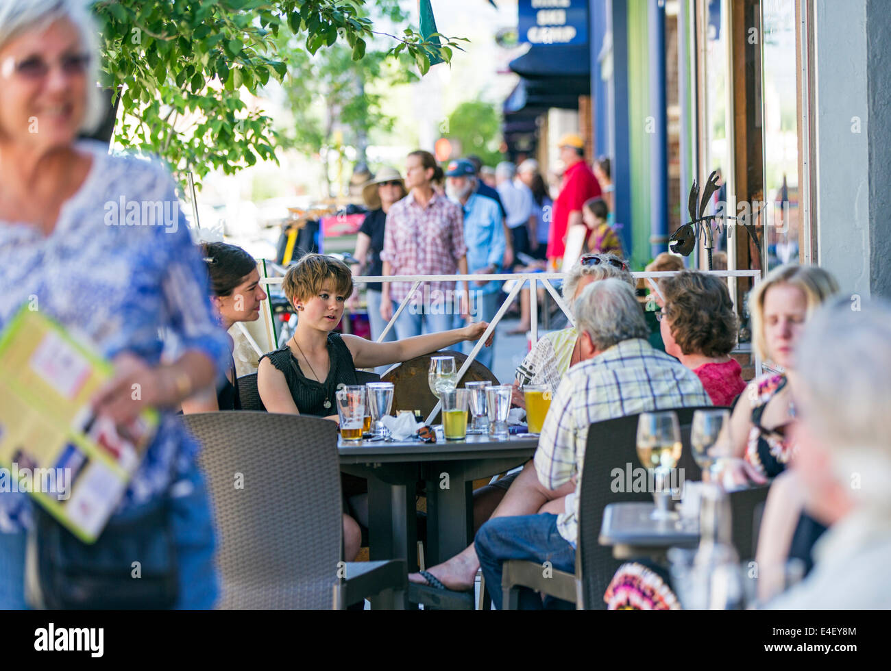 Visitors enjoying food & drink at Currents cafe during the annual small town ArtWalk Festival - Stock Image