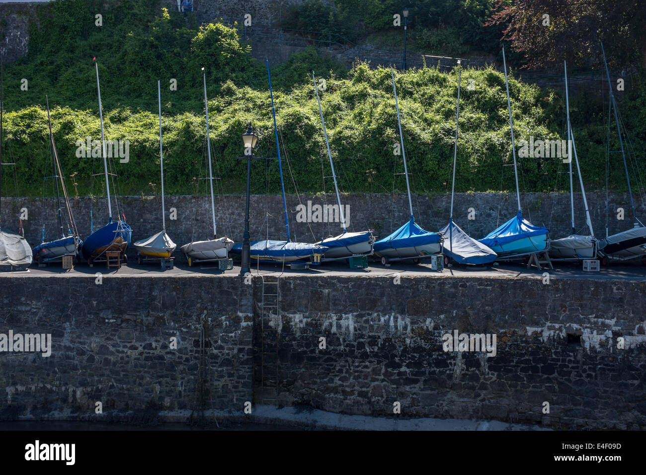 Sail boats on a harbour wall - Stock Image