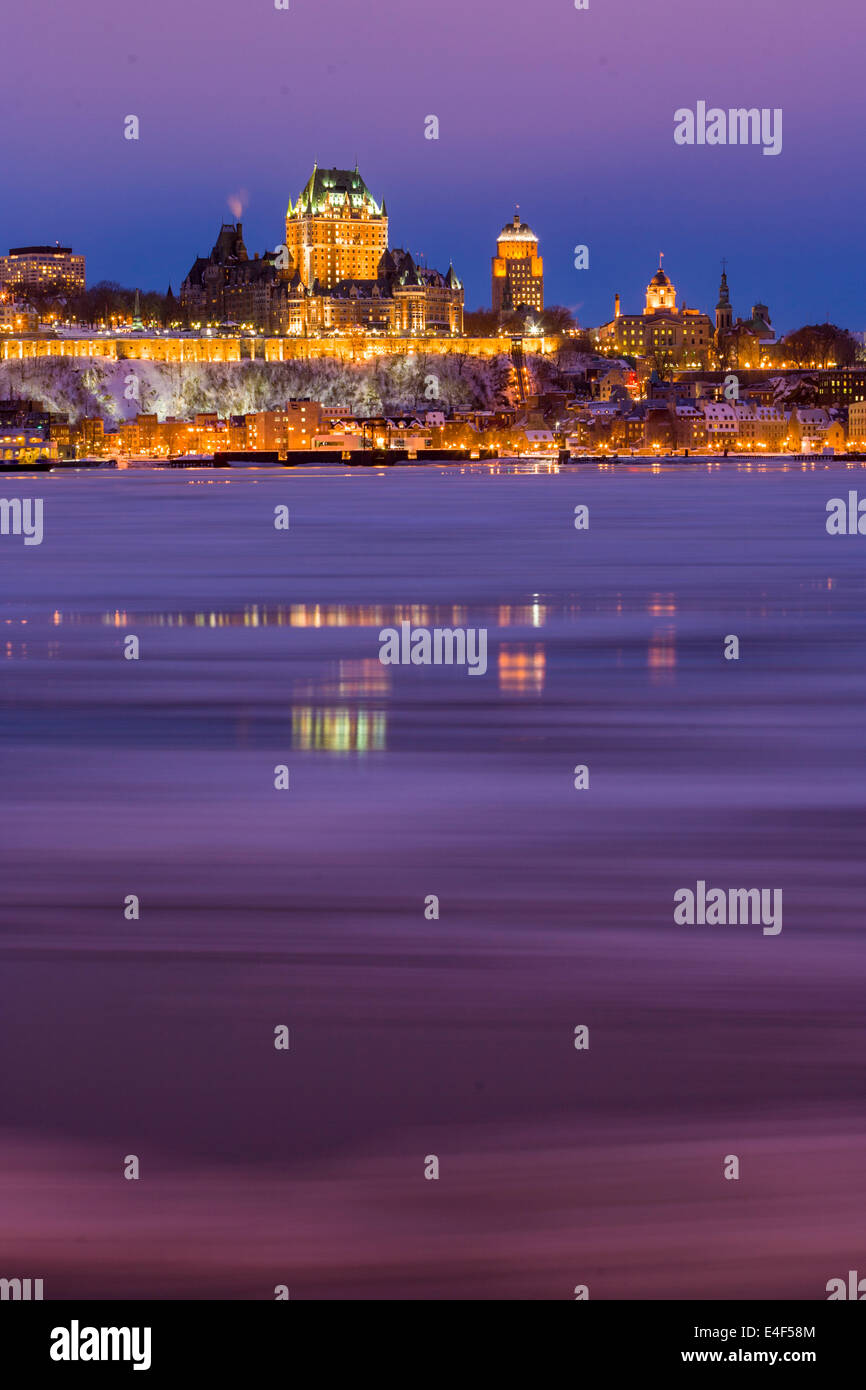 City skyline at twilight, showing Chateau Frontenac in winter, as seen from across the Saint Lawrence River, Quebec - Stock Image