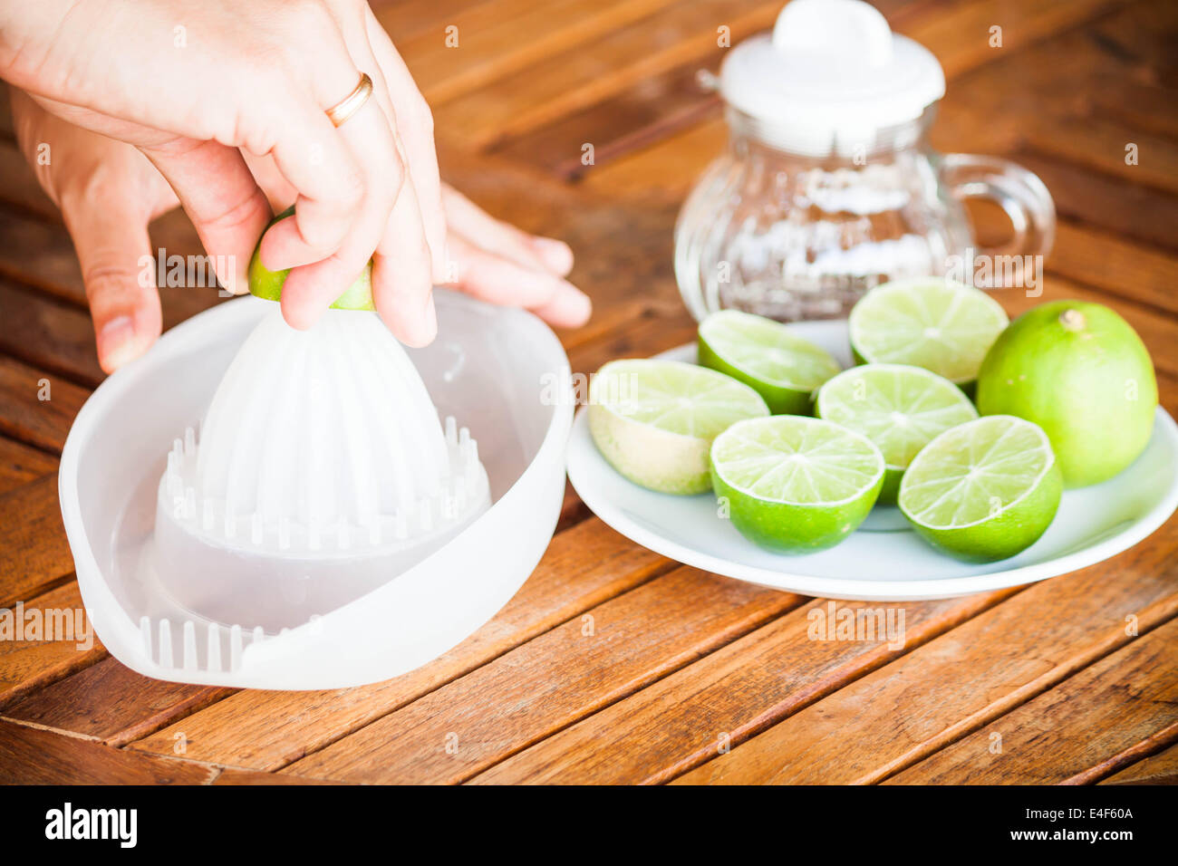 Hand squashing fresh citrus lime on wood table - Stock Image