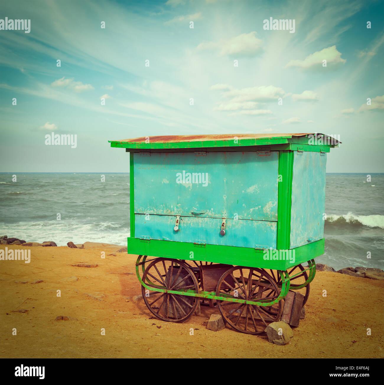 Vintage retro hipster style travel image of cart on beach. Tamil Nadu, India - Stock Image