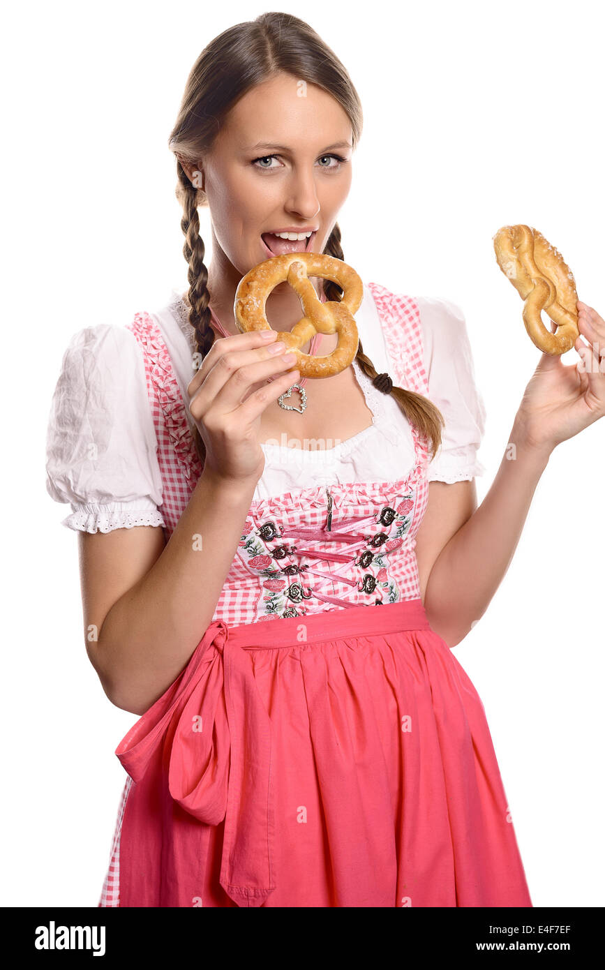 Happy attractive german or bavarian woman in a traditional dirndl opening her mouth to eat a fresh pretzel - Stock Image