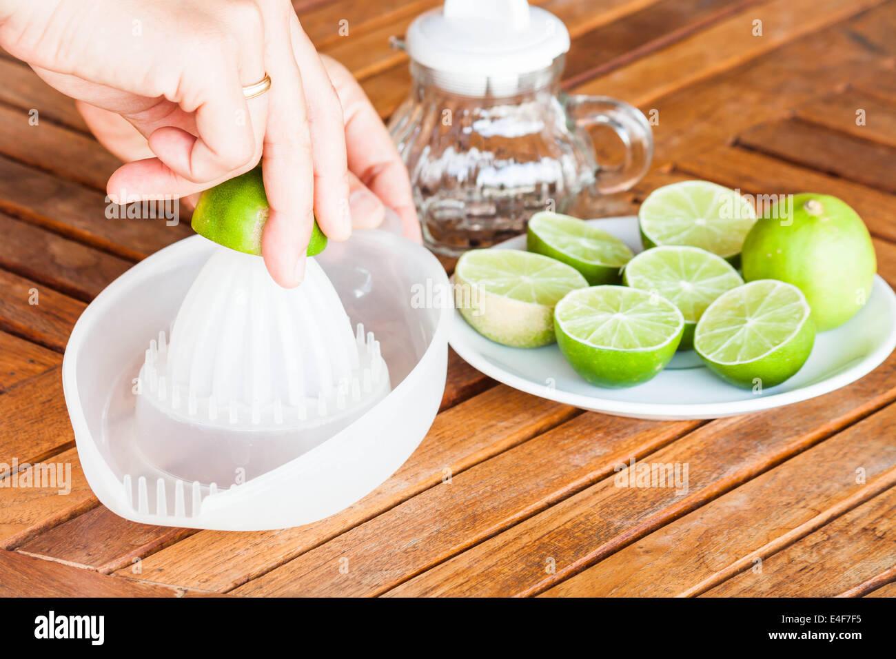 Hand squashing fresh lime on wood table - Stock Image