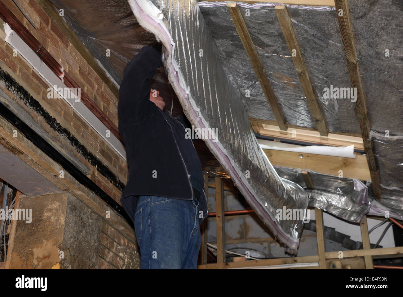 Workman installing foil insulation in a roof space. - Stock Image