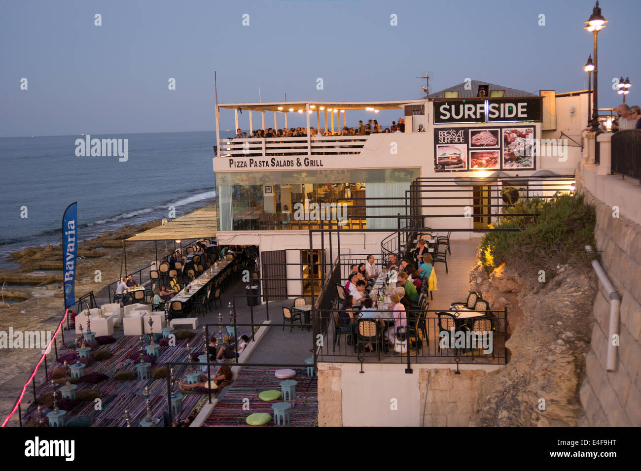 Customers enjoy a fine evening dining outdoors at the Surfside restaurant located in Tower Road, Sliema Malta - Stock Image
