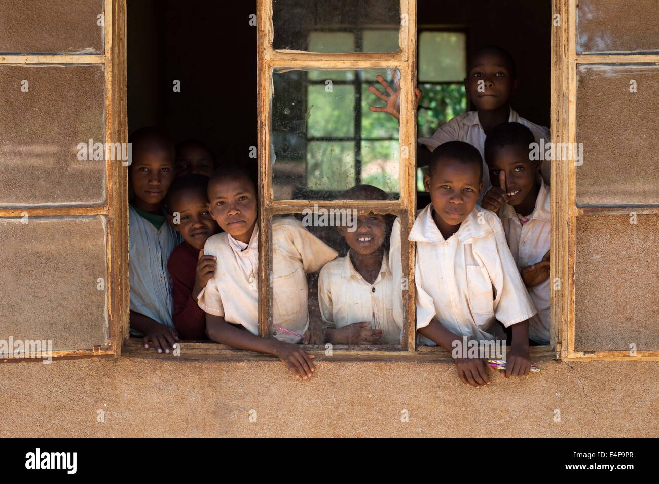 group portrait of children from a remote school in Tanzania, Africa looking out the window - Stock Image