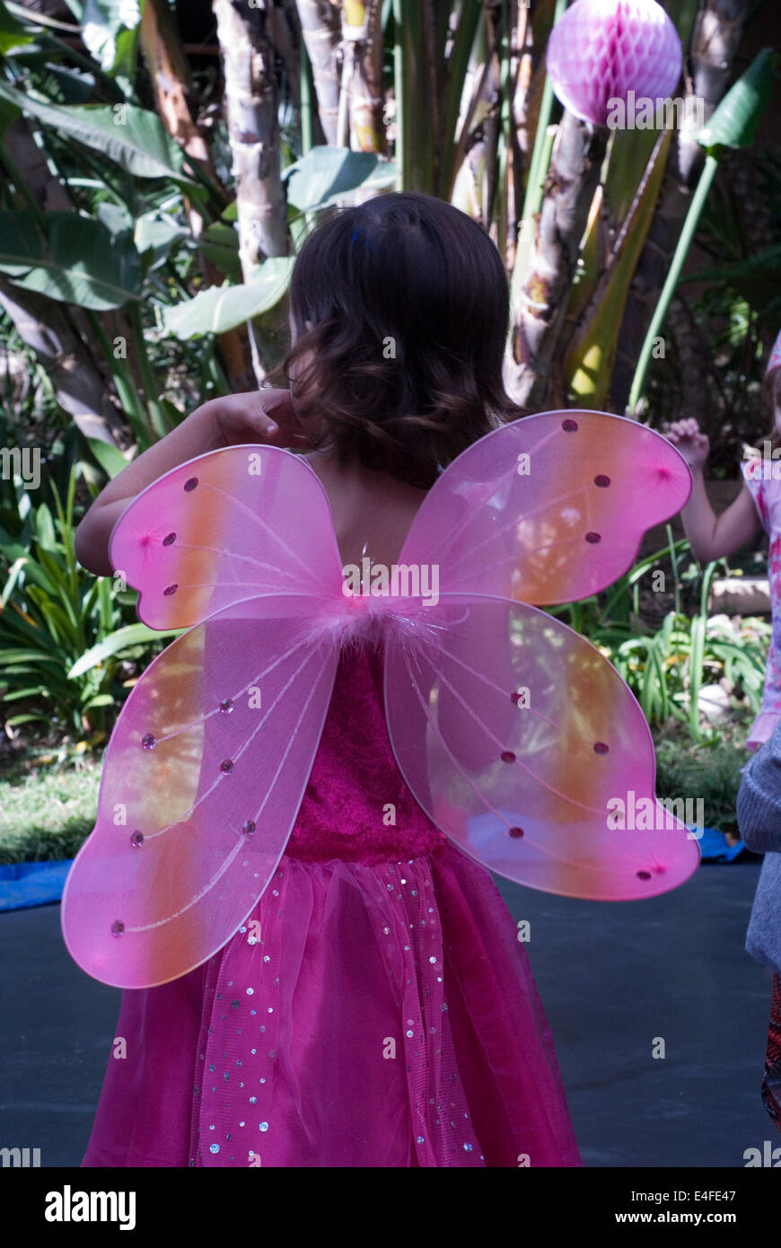 Back of Little girl with pink butterfly wings at birthday party. - Stock Image