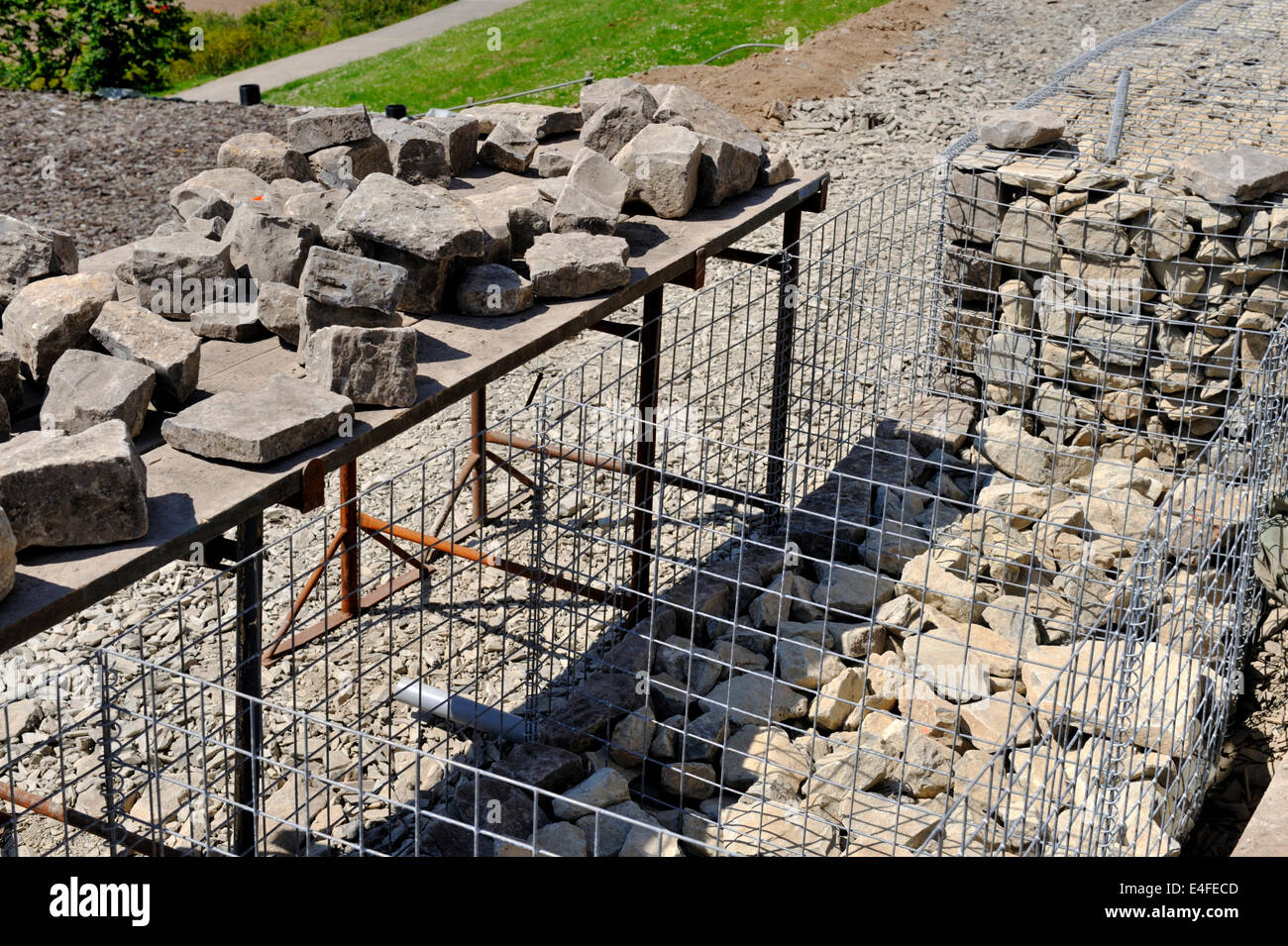 Filling detail of galvanized wire mesh babion being filled with rock for slope stabilization,  Aberporth, Wales, - Stock Image