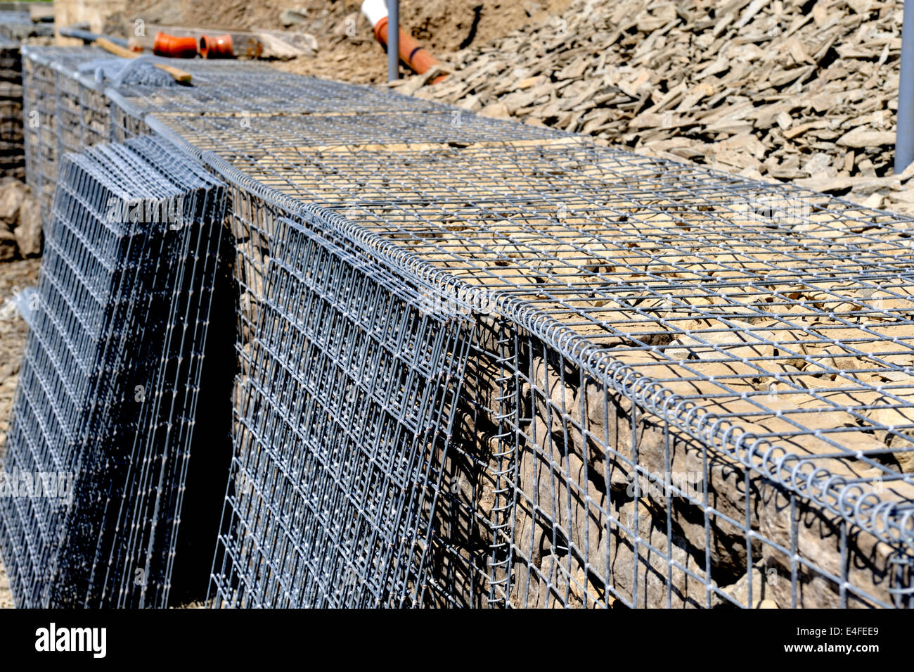 Detail of galvanized wire mesh babion being filled with rock for slope stabilization and spare basket sides,  Aberporth, - Stock Image
