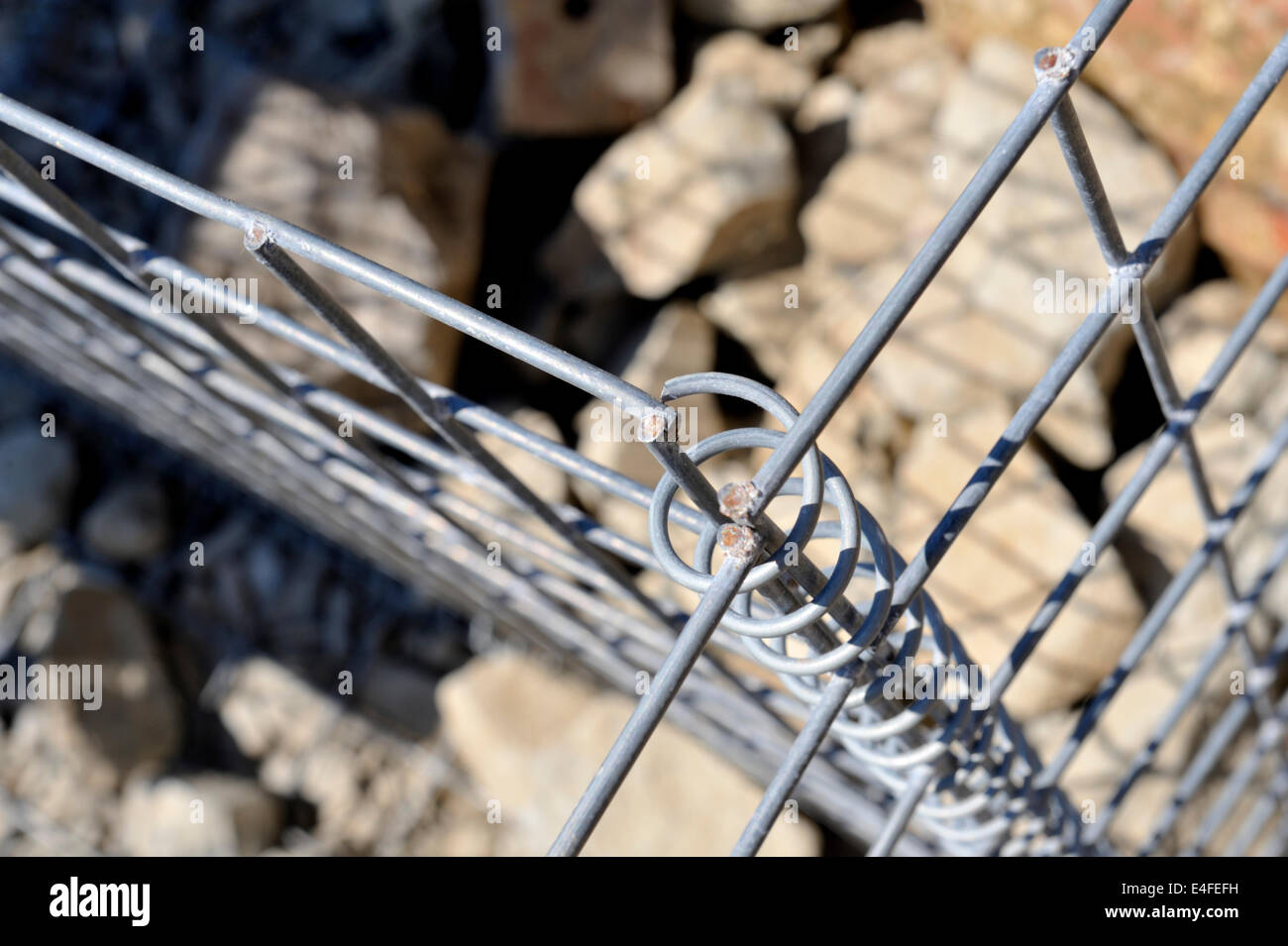 Close-up detail of galvanized wire mesh basket babion filled with rock for slope stabilization,  Aberporth, Wales, - Stock Image
