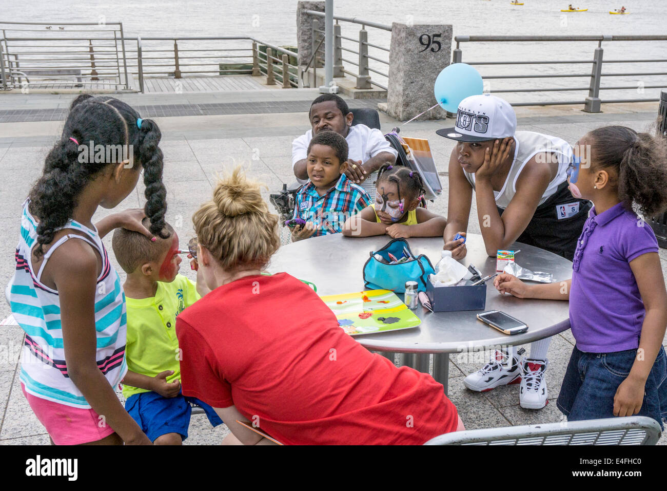 Caucasian woman artist face painting small black boy as other children watch at birthday party in Hudson River park - Stock Image