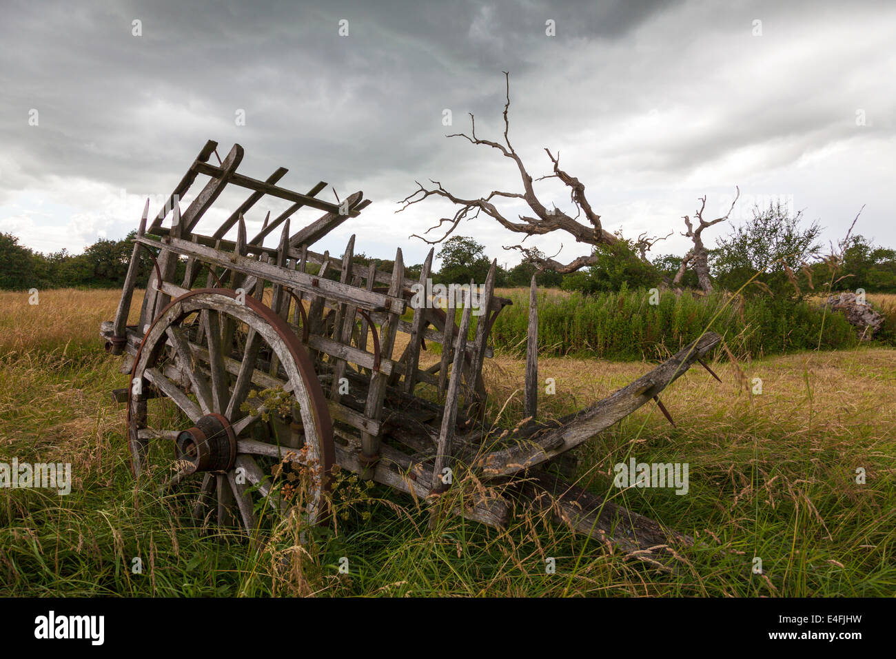Old decrepit farming machinery antique farm cart holding pen with cartwheels - Stock Image