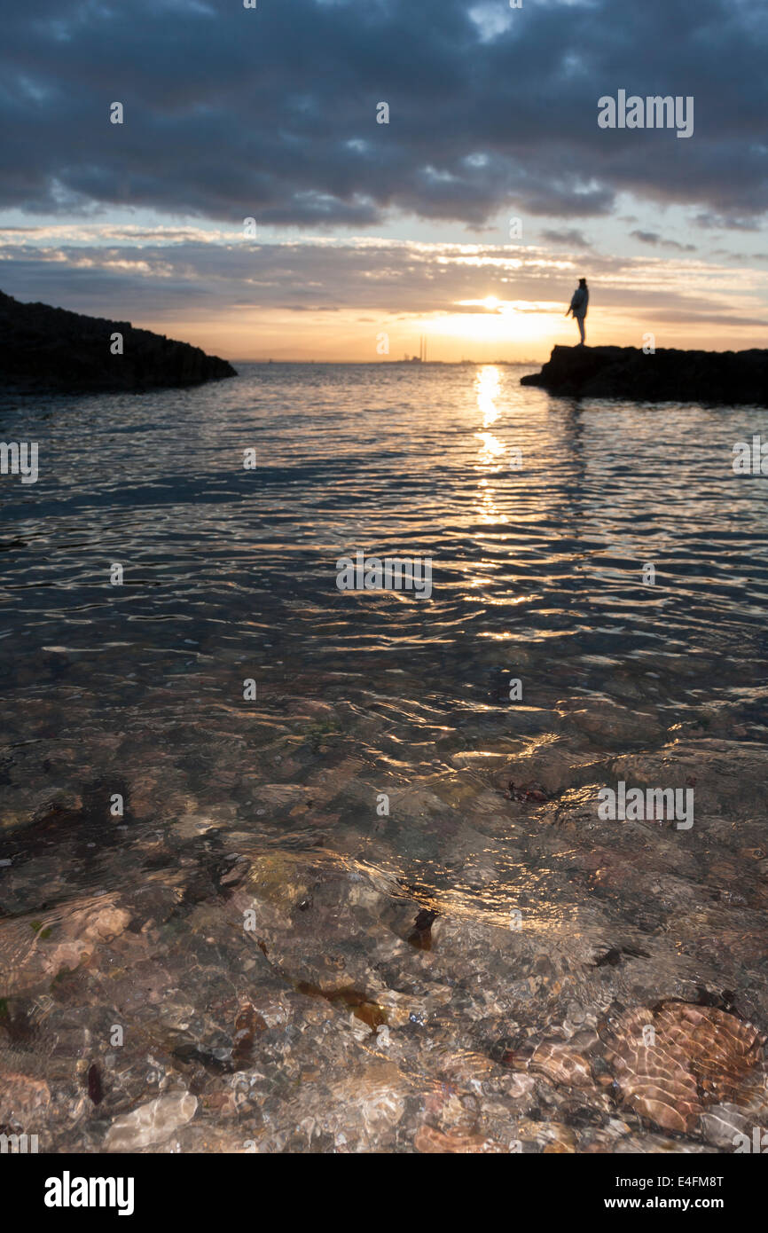 Sunset backlighting with human silhouette in Howth, Dublin. Ireland - Stock Image
