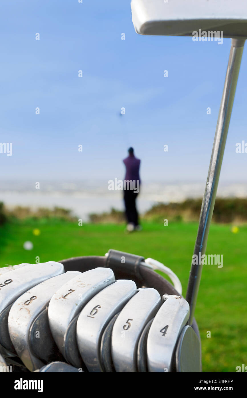 Close-up Golf Iron with golfer teeing off - Stock Image