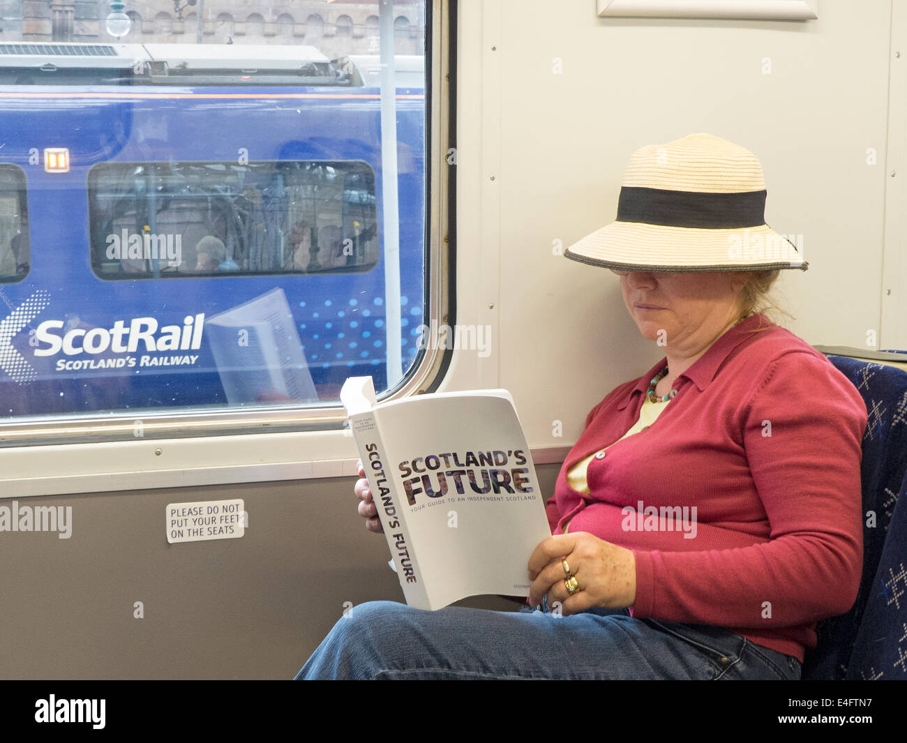 Scotland's Future a manual published by the Scottish Government about Independence  being read on a Scot Rail - Stock Image