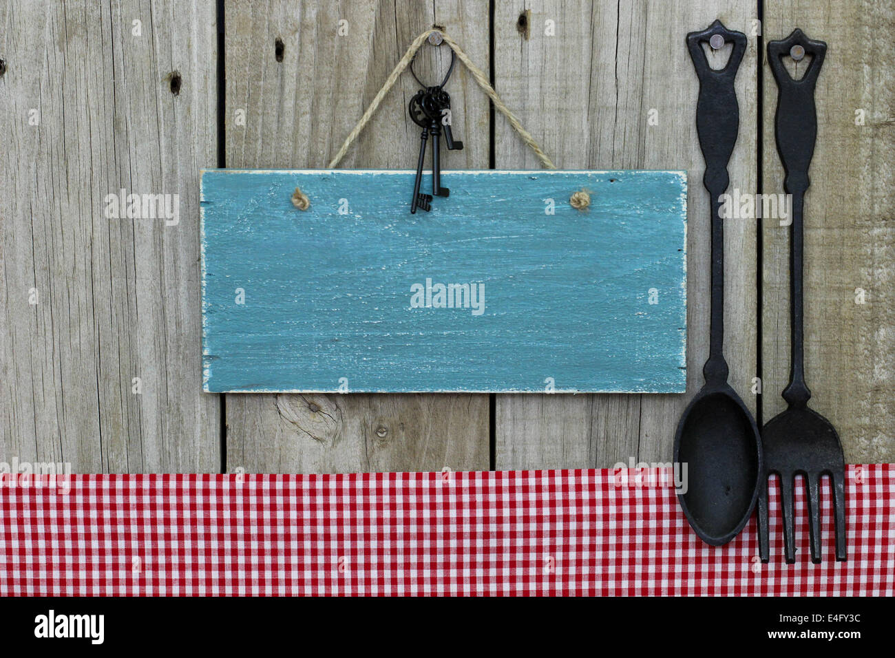 Blank antique blue sign with black iron keys hanging next to red checkered tablecloth and cast iron spoon and fork - Stock Image