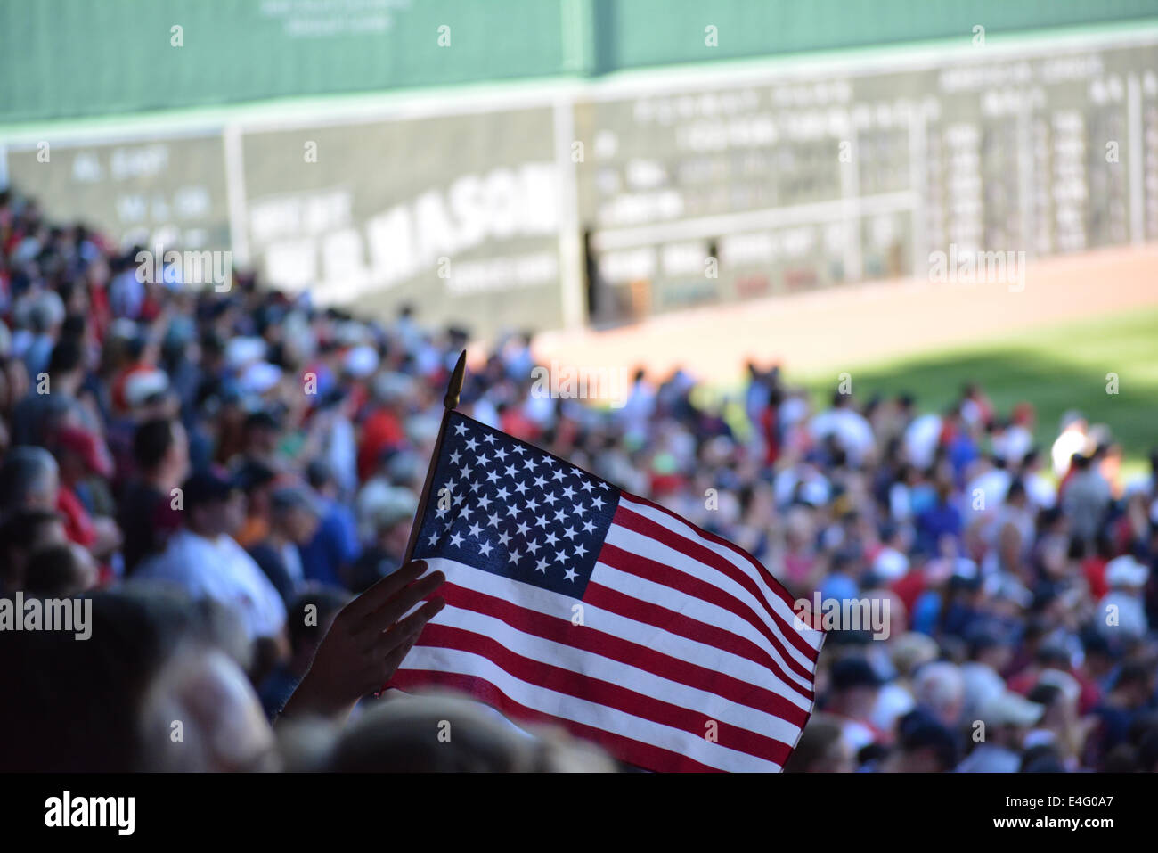 Fan waving a flag during a Boston Red Sox game at Fenway Park Stock