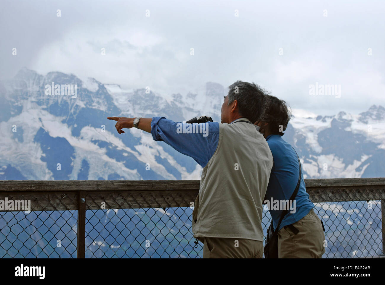 Tourists at Schilthorn viewpoint looking out onto Jungfrau, Oberland Bernese, Switzerland - Stock Image