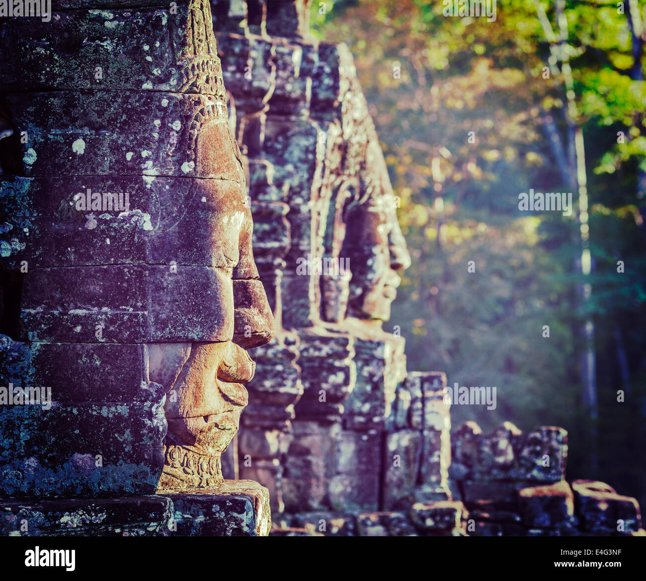 Vintage retro effect filtered hipster style travel image of Ancient stone faces of Bayon temple, Angkor, Cambodia - Stock Image
