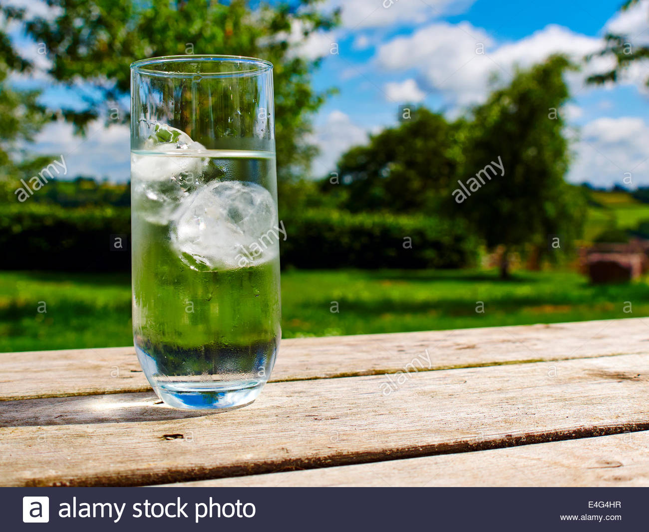 ice cold drink glass water on a wooden table outside in the sunshine in a garden Stock Photo