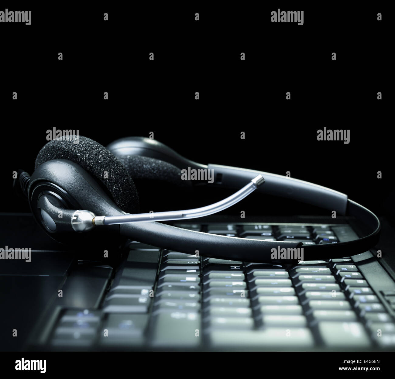 Headset on a laptop computer keyboard - Stock Image