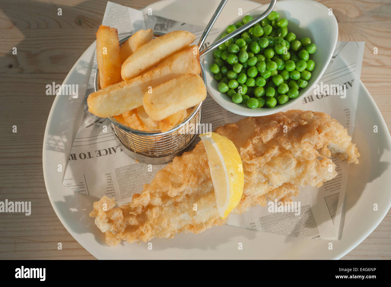 Fish and chips (Deep fried Haddock in batter) with peas and a segment of lemon  on a white plate on a wooden table - Stock Image