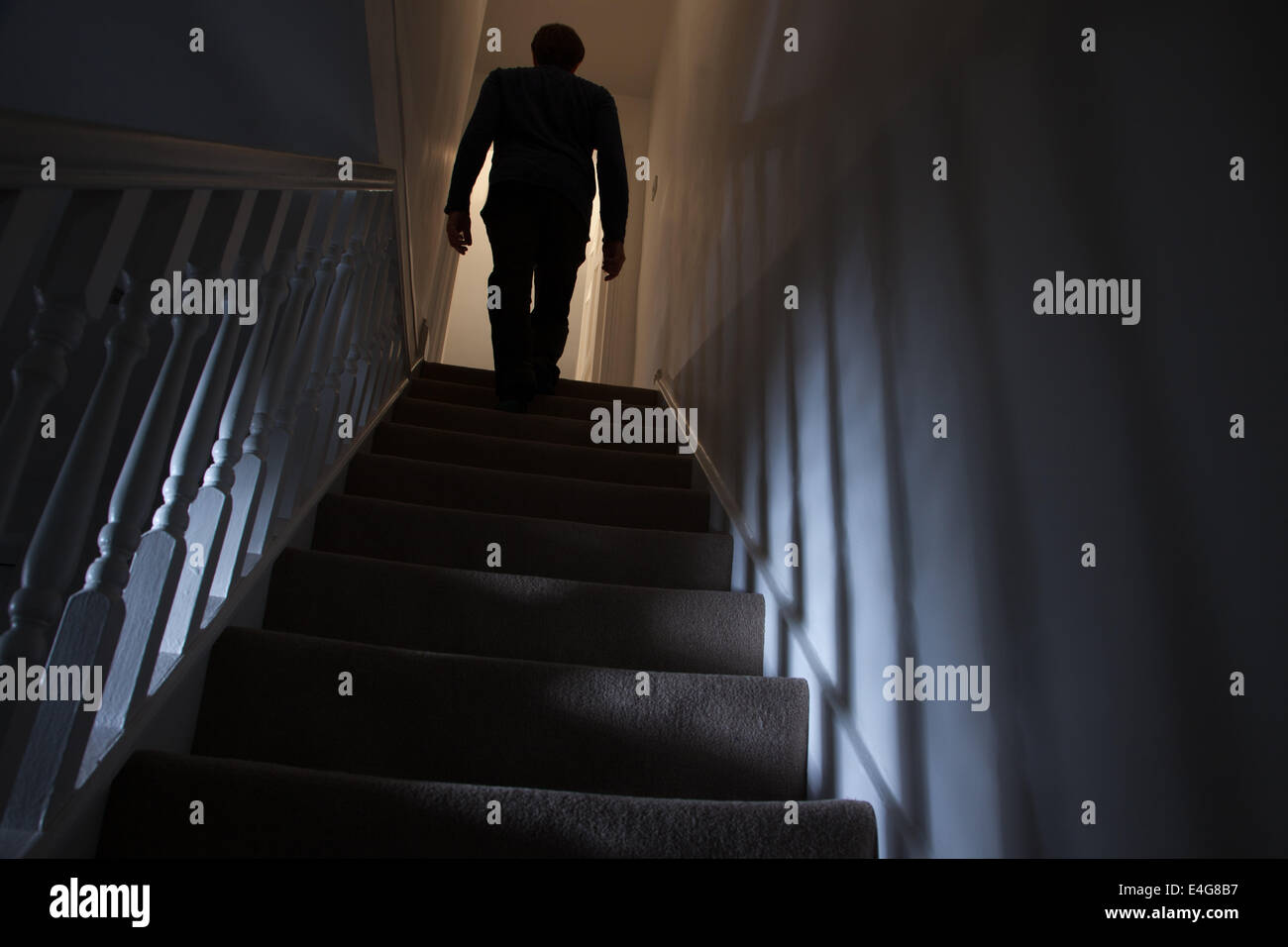 Silhouette of a man walking upstairs back view, shadows cast on the walls from the light below. Stock Photo