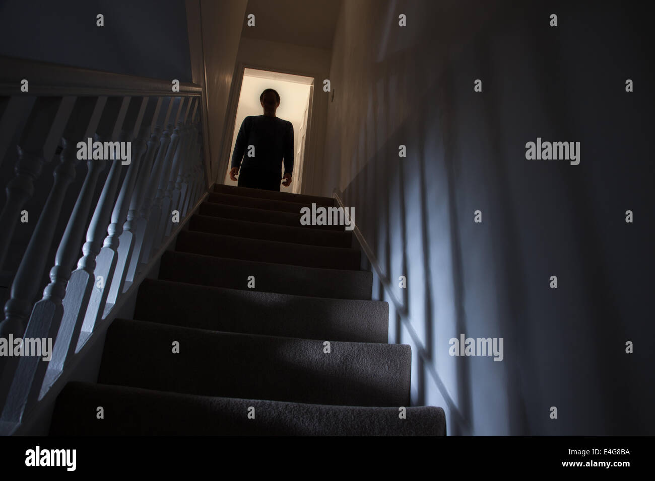 Silhouette of a man standing at the top of a stairway, shadows cast on the walls from the light below. Stock Photo