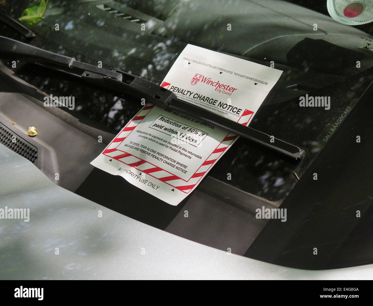 Penalty Charge Notice document on car windscreen - Stock Image