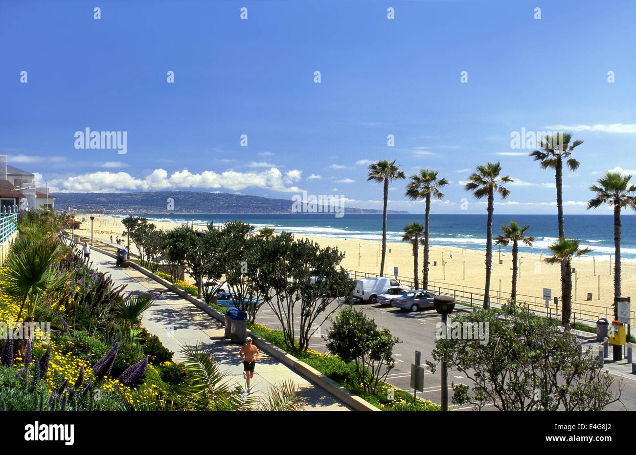 Jogger on Manhattan Beach bike path with Palos Verdes Peninsula in background in Southern California, USA - Stock Image