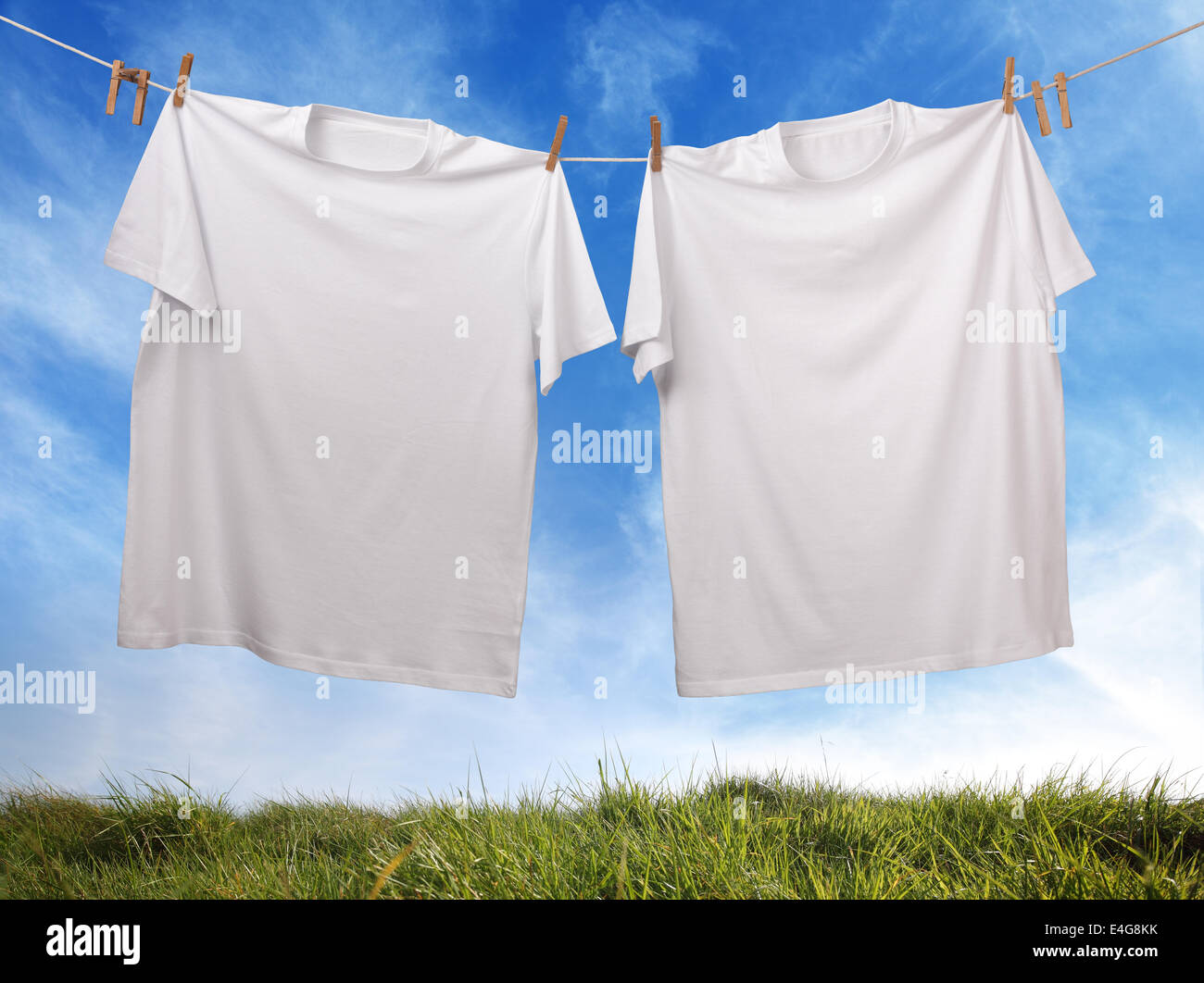 Blank white t-shirt hanging on clothesline - Stock Image