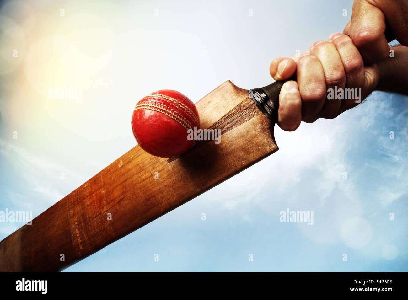 Cricket player hitting ball - Stock Image