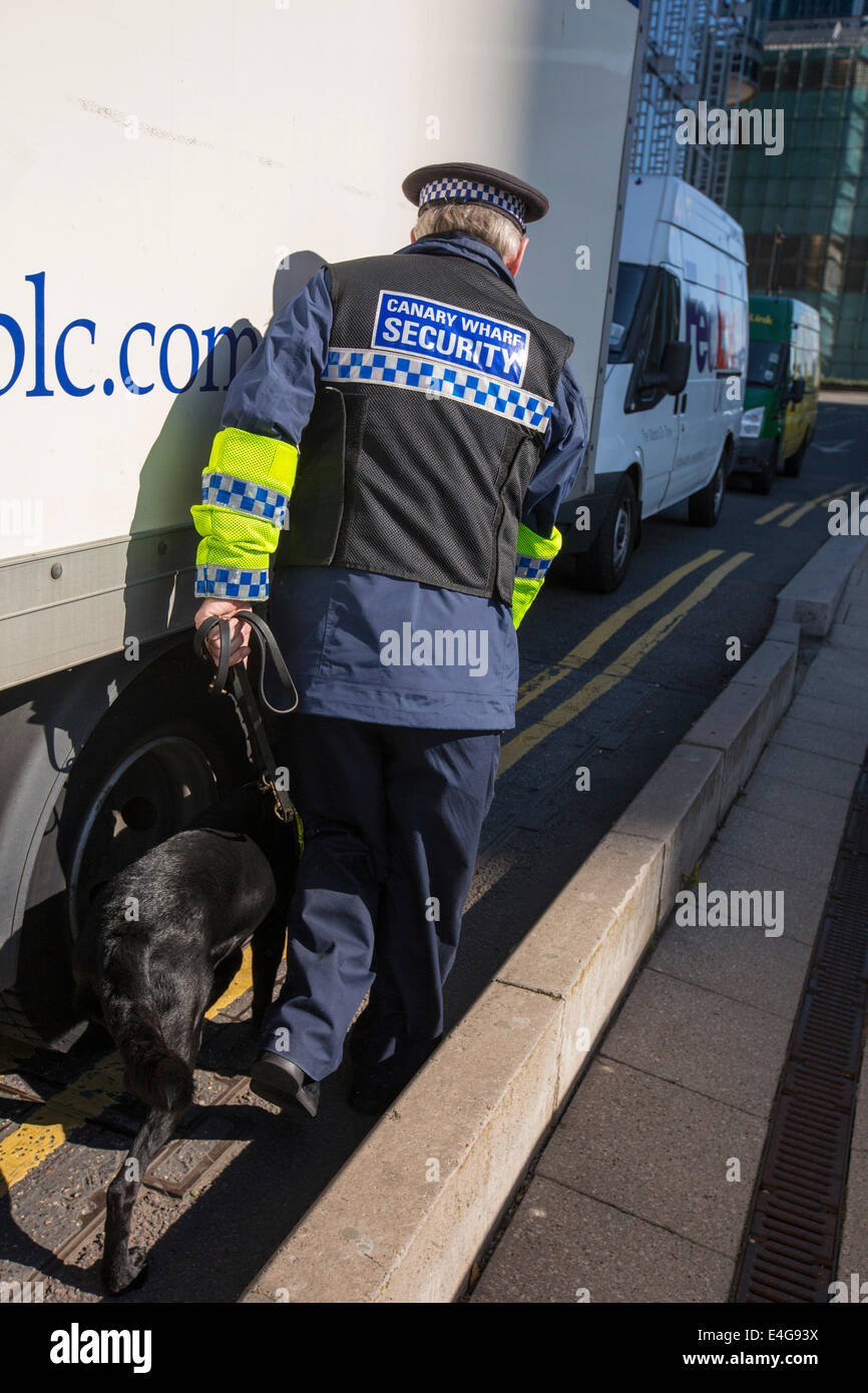 A sniffer dog checking trucks for bombs entering banks in Canary Wharf, London, UK. - Stock Image