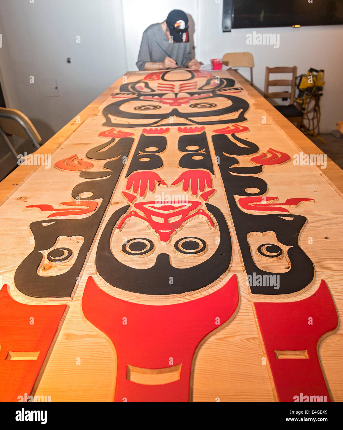 Haida artist Eric Parnell paints a boardroom table that he carved out of cedar for the Skwachays Lodge - Stock Image