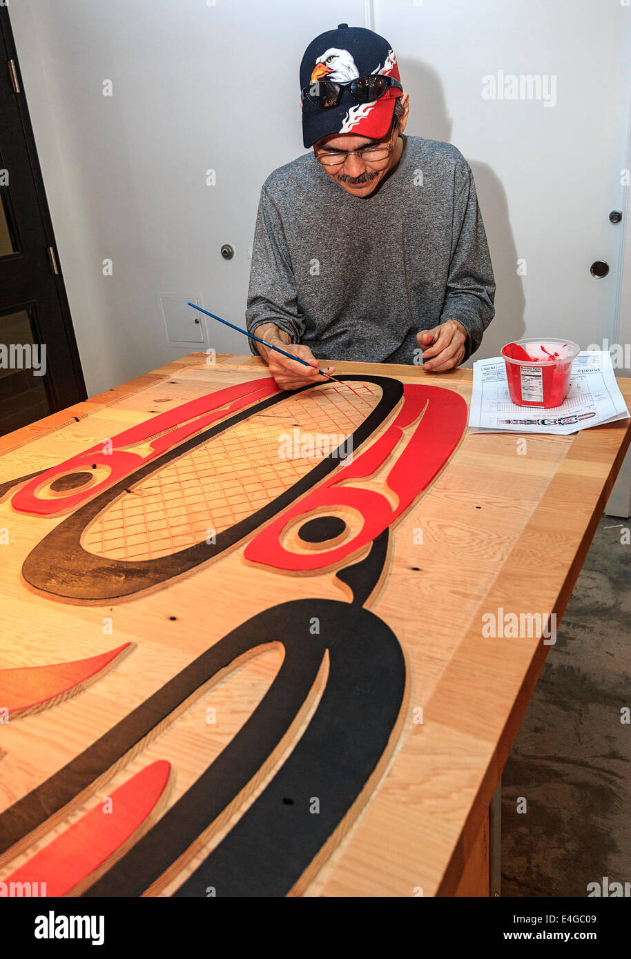 Haida artist Eric Parnell paints a boardroom table that he carved out of cedar for the Skwachays Lodge, a First - Stock Image