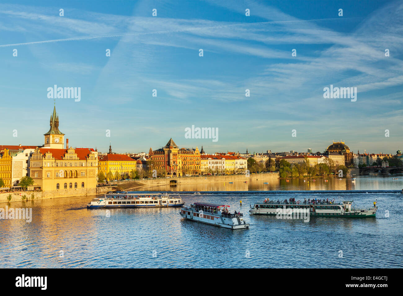 Vltava river with tourist boats and Prague Stare Mesto embankment view from Charles bridge on sunset. Prague, Czech - Stock Image