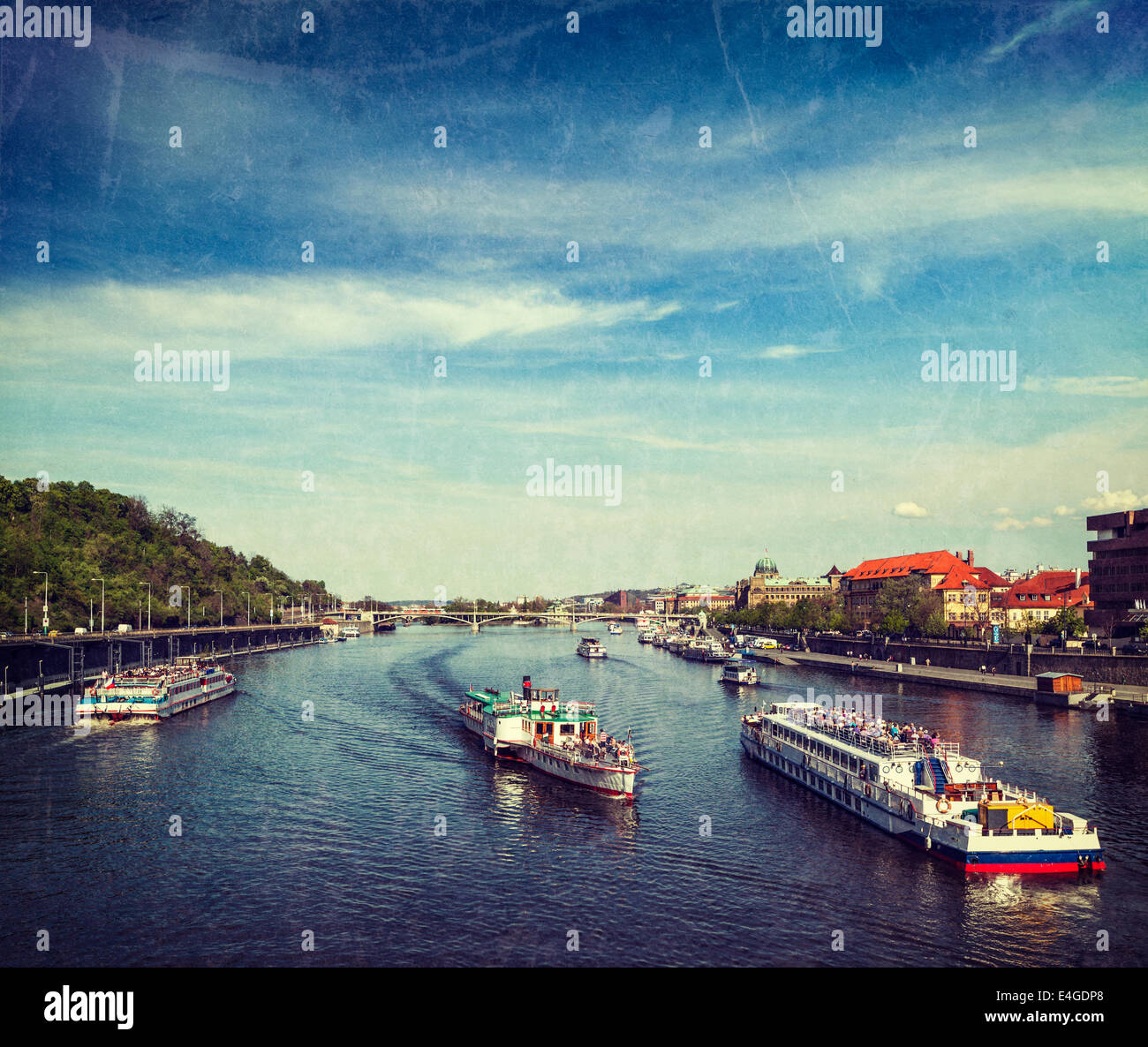 Vintage retro hipster style travel image of turist boats on Vltava river in Prague, Czech Republic with grunge texture - Stock Image