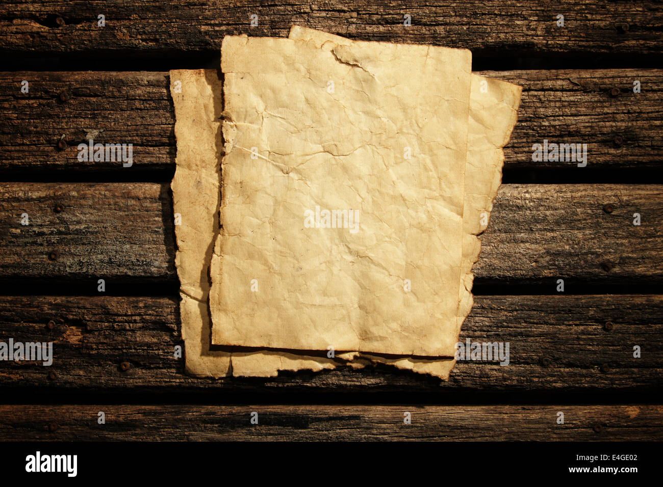 Old paper on wooden wall - Stock Image