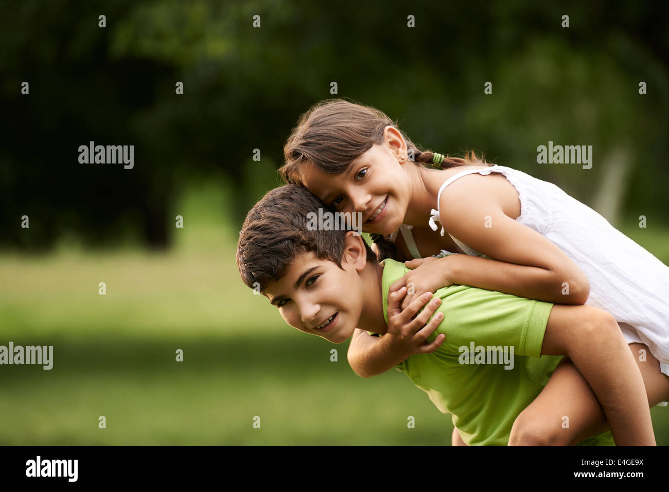 People in love with happy little girl and boy running piggyback in city park. Copy space - Stock Image