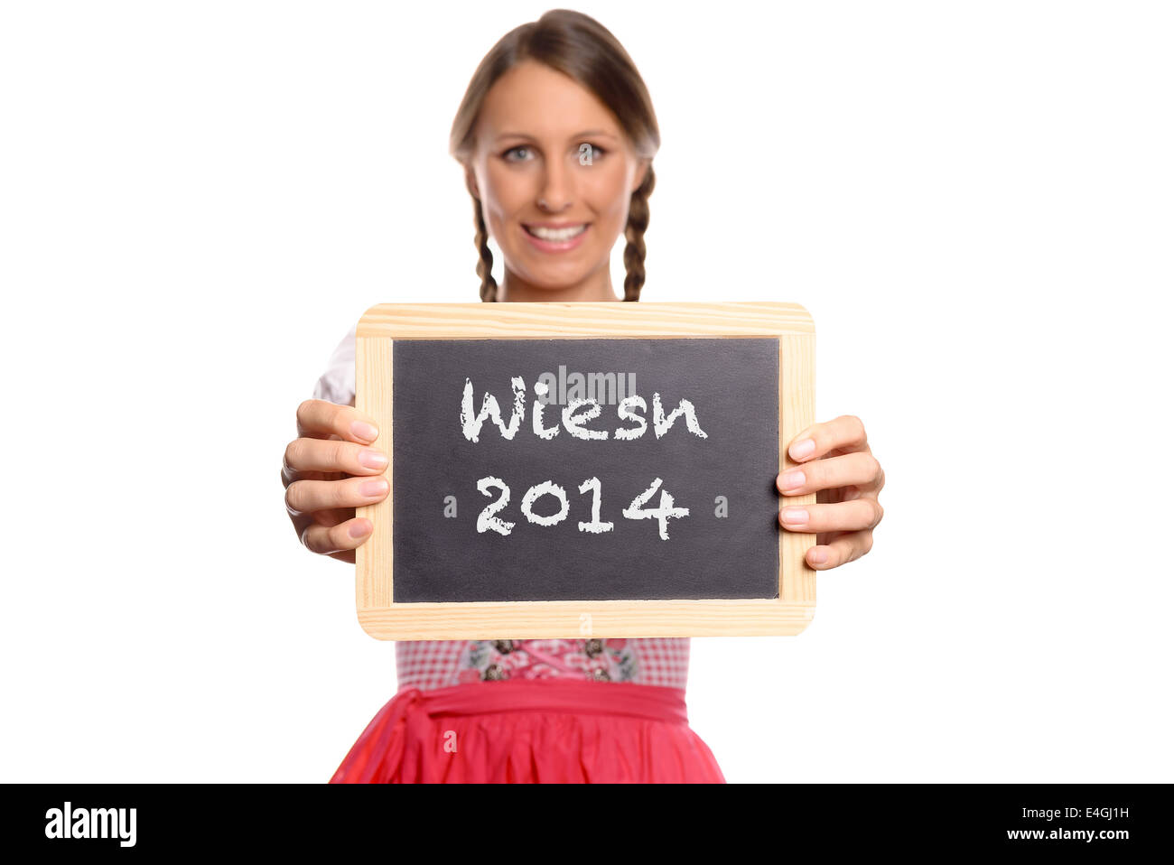 Young woman in a dirndl holding up a blank vintage school slate in front of her chest with Wiesn 2014 written on - Stock Image