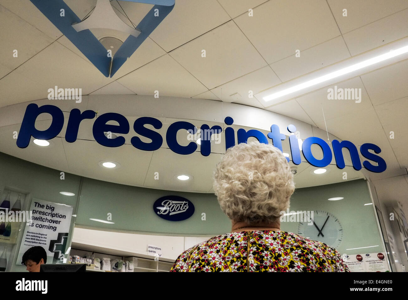 A mature woman waiting prescription counter in a Boots store. - Stock Image