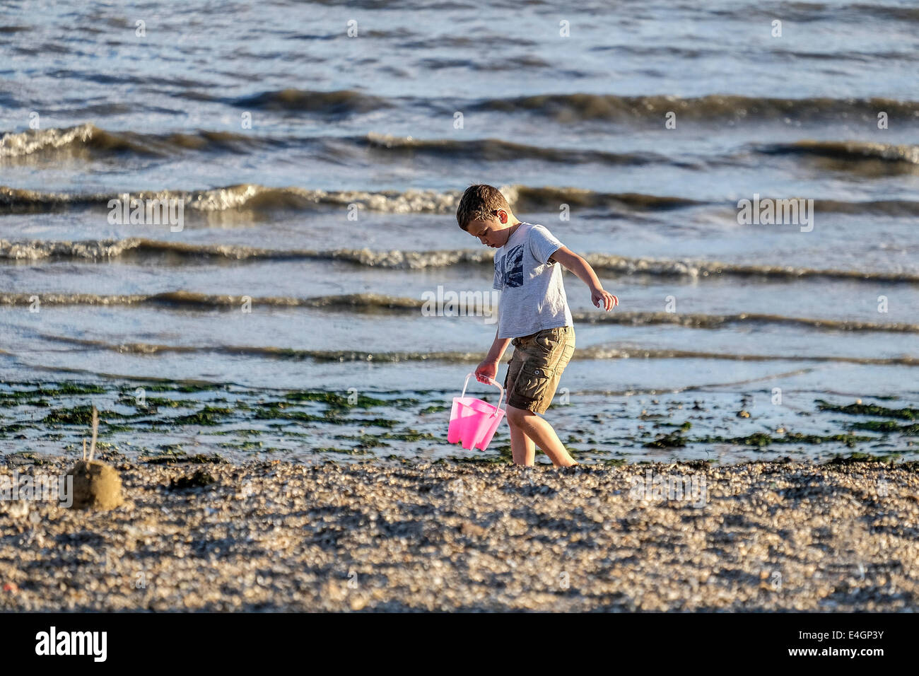 A young boy carrying his bucket across a beach. - Stock Image