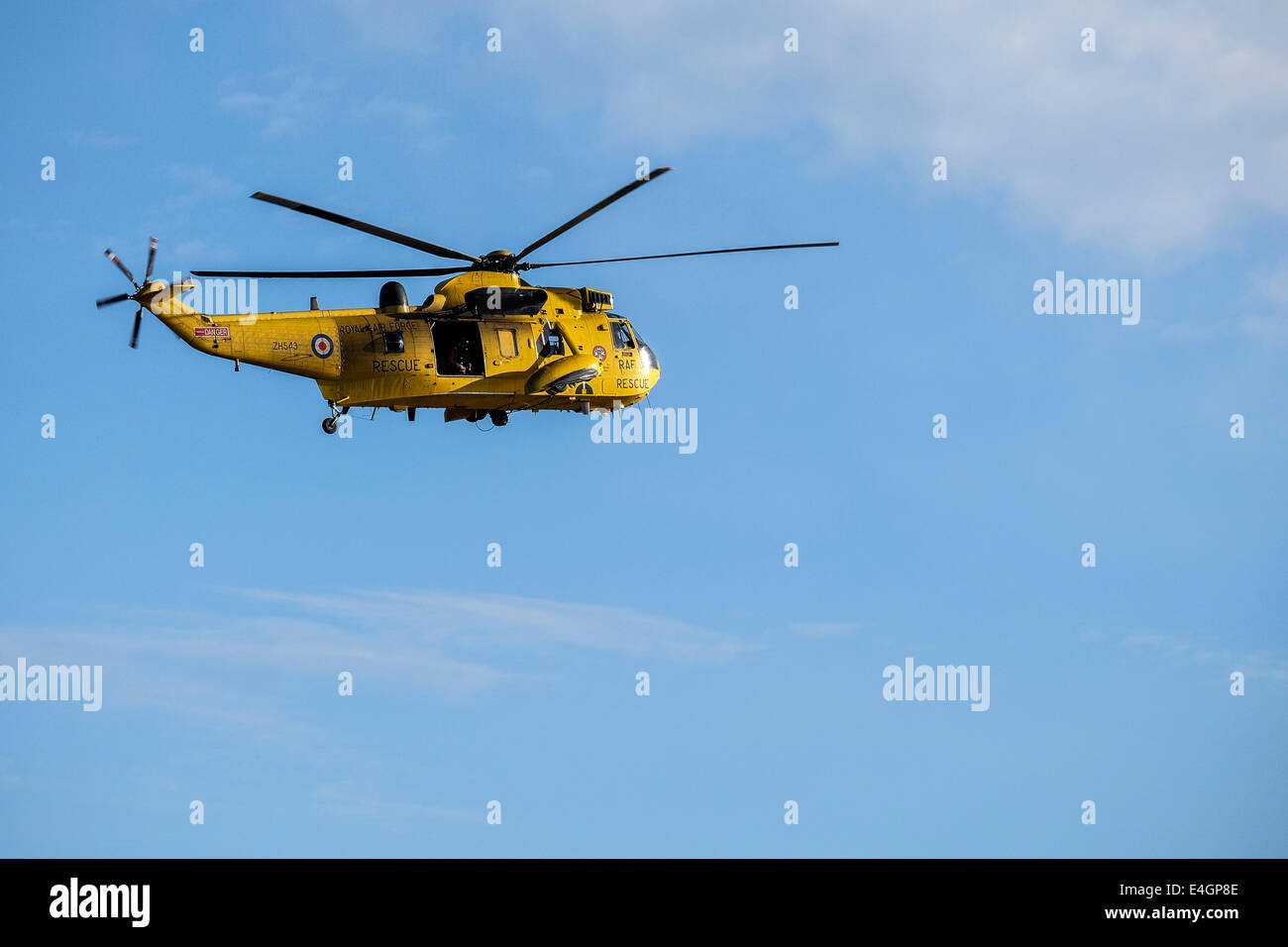An RAF rescue helicopter flying overhead. - Stock Image