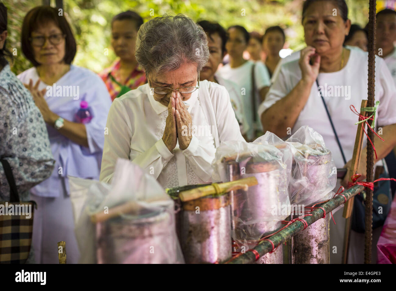 Bangkok, Bangkok, Thailand. 11th July, 2014. A woman prays after pouring molten wax into a candle mold at Wat Pathum - Stock Image
