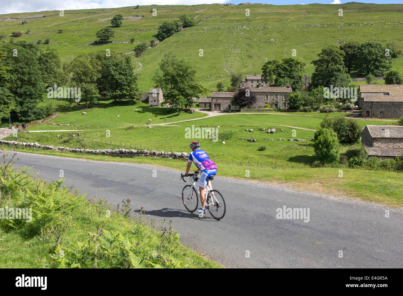Cyclist passing Yockenthwaite, Wharfdale in the Yorkshire Dales National Park, North Yorkshire, England, UK - Stock Image