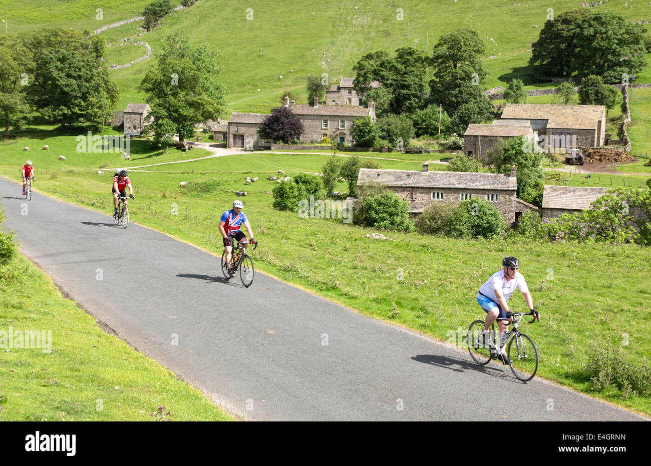 Cyclists passing Yockenthwaite, Wharfdale in the Yorkshire Dales National Park, North Yorkshire, England, UK - Stock Image