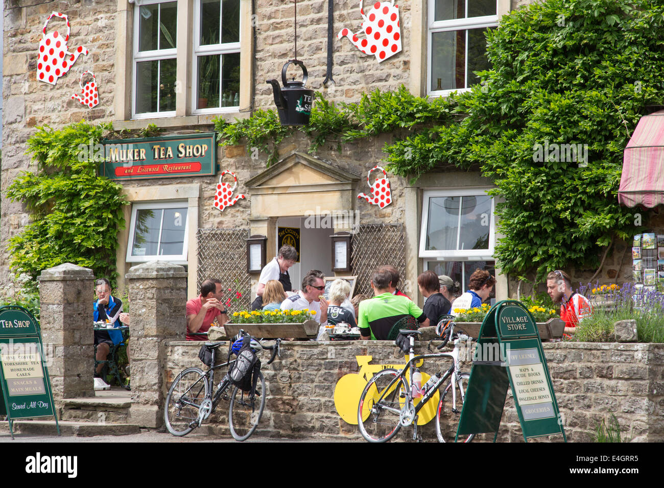 Cyclists at a cafe in Muker, Swaledale, Yorkshire Dales National Park, North Yorkshire, England, UK - Stock Image