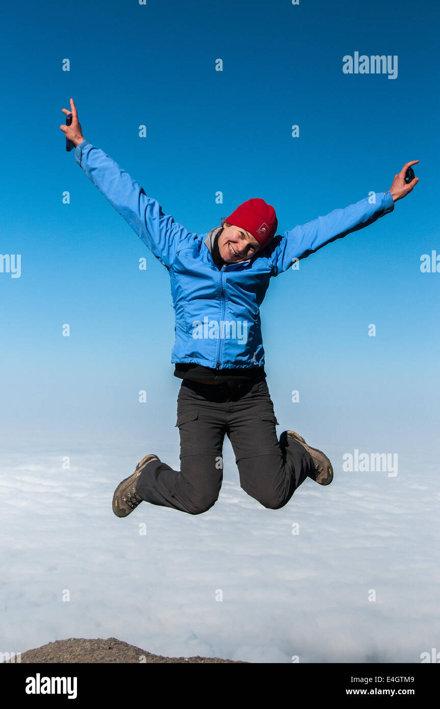Trekker jumping for joy on the way to the summit of Kilimanjaro - Stock Image